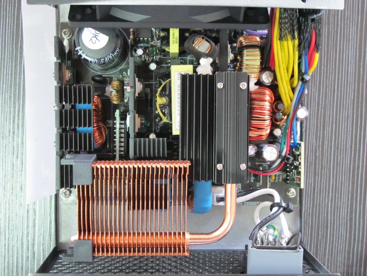 [超频三坦克W40赏析3]  双管正激结构 绿松石500全能版依然使用了主动式PFC和双管正激结构,当然为了提高转换效率,电源在用料与设计上也进一步提升,最终使得转换效率达到了86%以上。  一级EMI滤波电路 一级EMI滤波电路比较简单,与之前的电源一样直接固定在市电入口处,使用了一个X电容。  二级EMI滤波电容 二级滤波电路使用了一个X电容和2个Y电容以及2个共模电感,并附有相应的保险管,做工很完整。  高压整流电容 整流桥部分由于散热片的遮挡而看不清具体型号,不过猜测应该与绿松石450热管版一样是